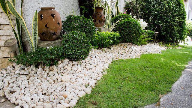 Белые камни и глиняные вазы в декоре газона