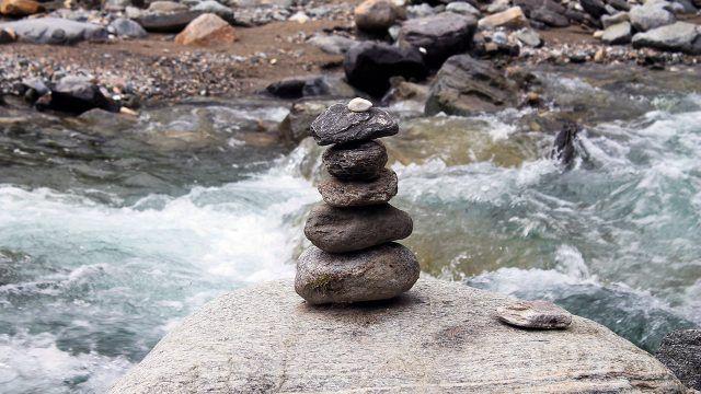 Фигура из сада камней на берегу водопада