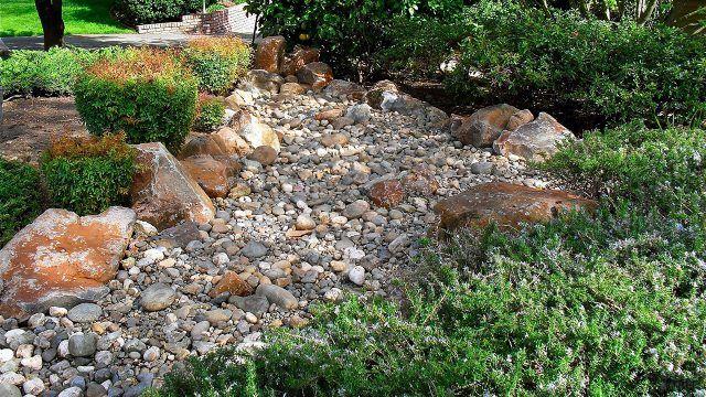 Каменная река среди зелени сада
