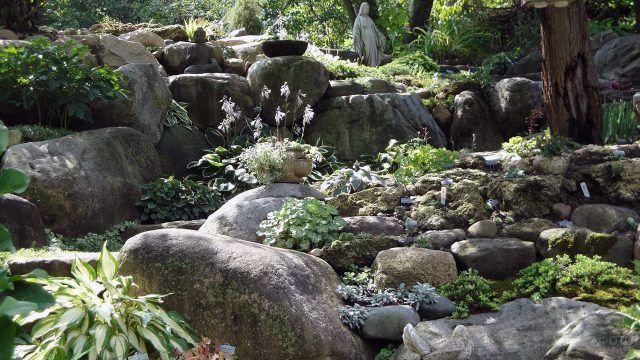 Каменный сад с зеленью и скульптурами Будды и Девы Марии