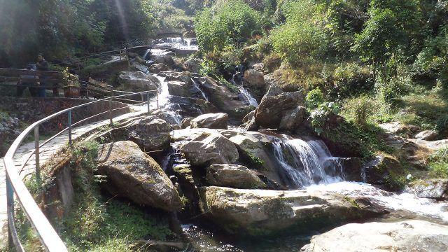 Мост у водопада в природном саду камней