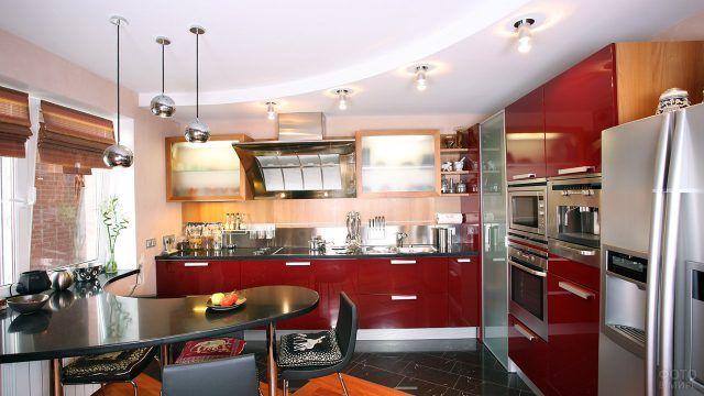 Бордовый кухонный гарнитур и чёрный футуристичный стол в типовой кухне