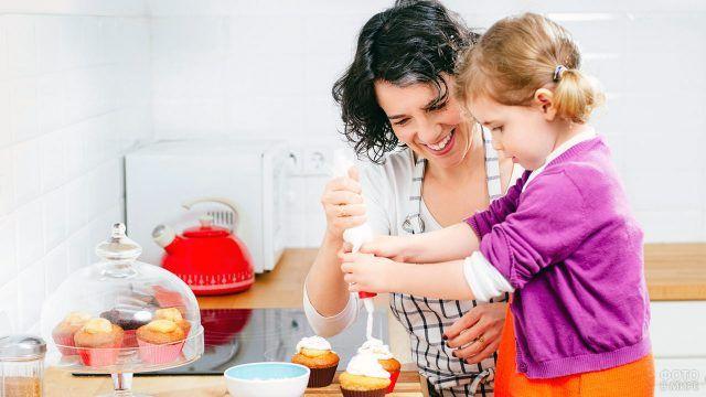 Мама с дочкой украшают кексы в белоснежной кухне