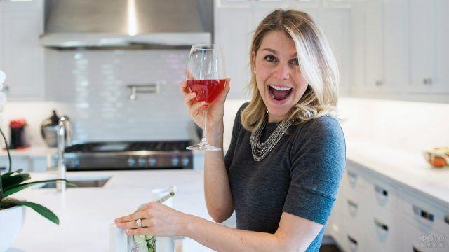 Женщина с бокалом вина в чистой белой кухне