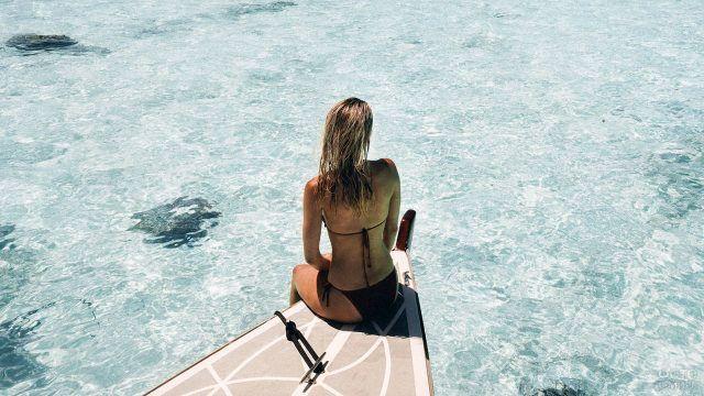Блондинка на носу лодки подплывающей к курортному острову