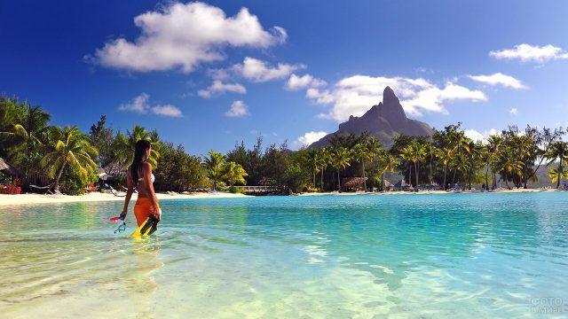 Девушка с маской и ластами входит в воду на пляже Бора-Бора