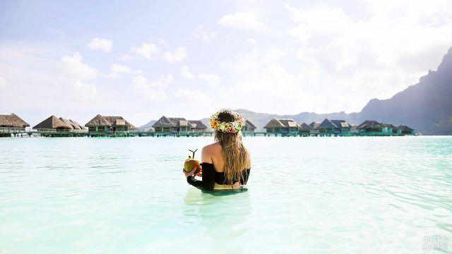 Девушка в воде держит кокос в руках