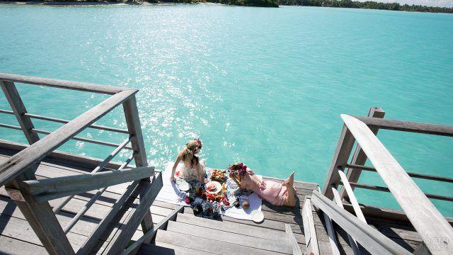 Девушки устроили пикник у воды на ступеньках бунгало