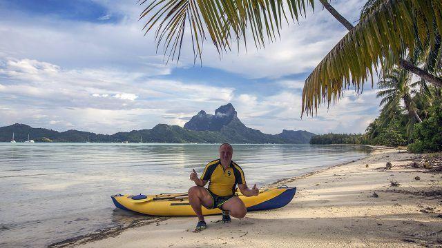 Довольный турист у байдарки на пляже Бора-Бора