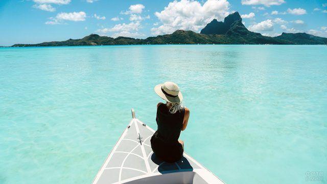 Гламурная девушка в шялпе на носу белой лодки в водах Бора-Бора
