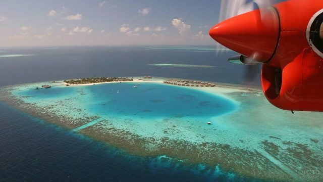 Красный самолёт пролетает на островом Бора-Бора