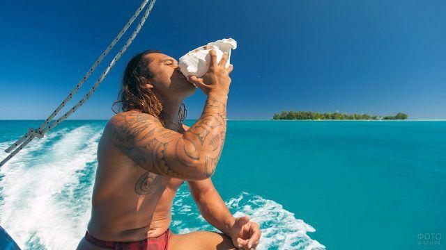 Мужчина на яхте пьет воду из большой ракушки