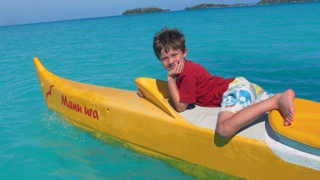 Счастливый мальчик на носу лодки в водах атолла Бора-Бора