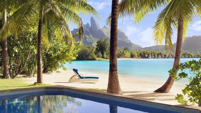 В тени пляжа у бассейна под пальмами