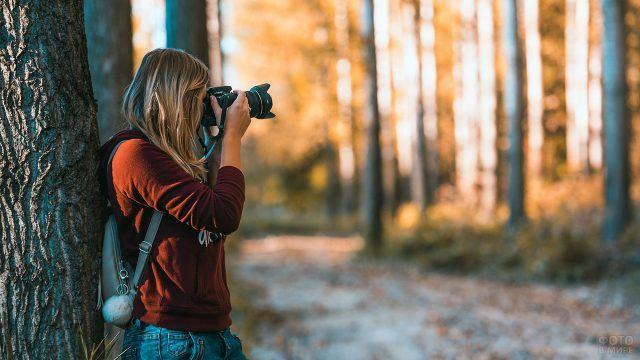 Девушка фотографирует осенний лес