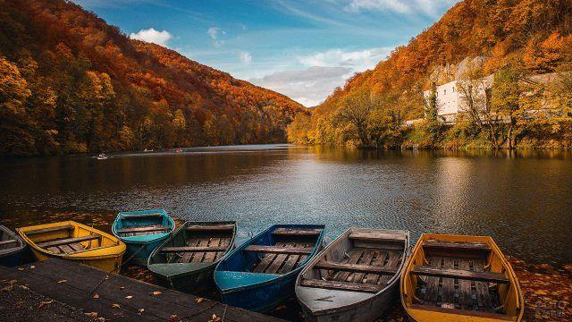Лодки в реке среди осенних гор