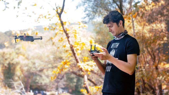 Мужчина запускает дрон на фоне осенних деревьев