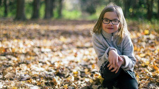 Портрет девочки в очках на осенней лужайке
