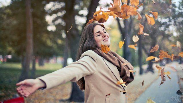 Счастливая девушка подбрасывает ворох осенних листьев