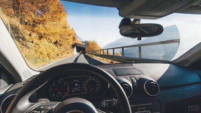 Вид из автомобиля на горную дорогу среди осенних деревьев