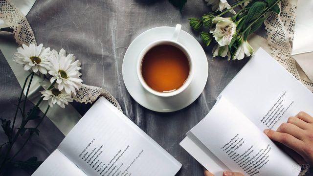 Белые цветы и чашка чая на столе с открытыми книгами