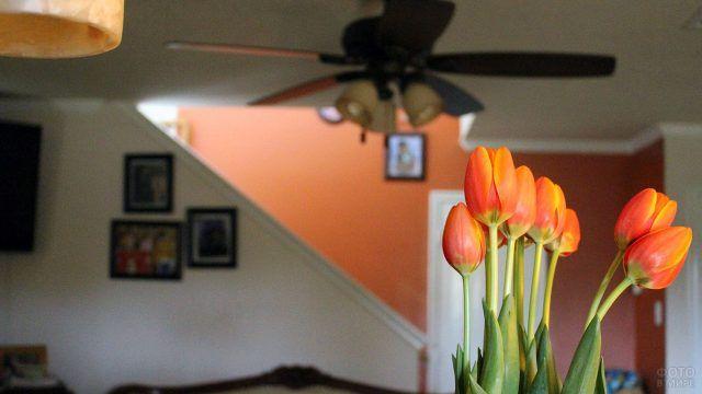 Букет красных тюльпанов в тёмной гостиной
