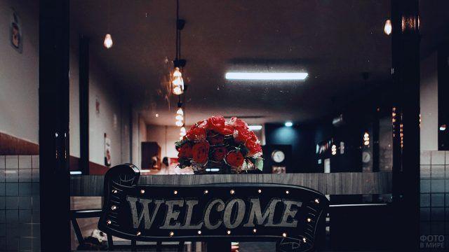 Букет роз на барной стойке с надписью Welcome
