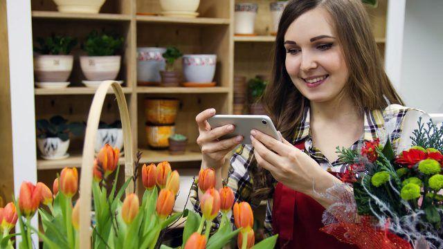 Девушка-флорист фотографирует букет тюльпанов