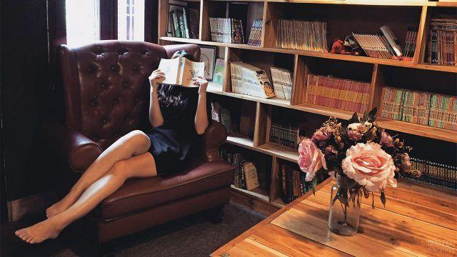 Девушка прячется за книгой на фоне букета розовых цветов в библиотеке