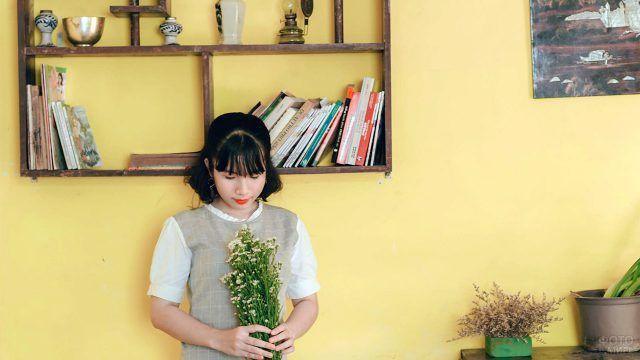Девушка с букетом полевых цветов у книжной полки