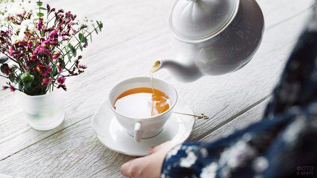 Ярко-розовые полевые цветы в вазе на столе с чаем