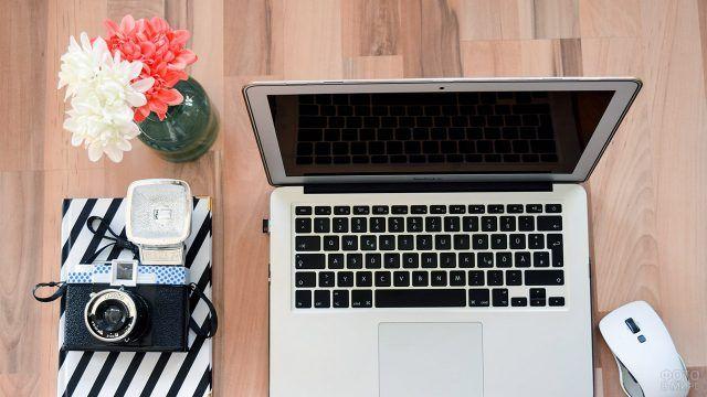 Красно-белый букет на столе с ноутбуком и фотоаппаратом