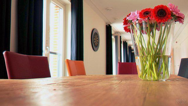 Красные герберы в прозрачной вазе на деревянном столе