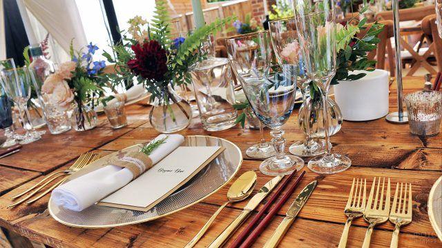 Накрытый деревянный стол украшенный букетиками цветов