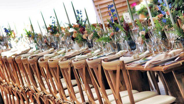 Накрытый к празднику стол с пёстрыми букетами цветов