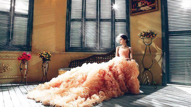 Невеста в розовом платье на банкетке среди букетов цветов