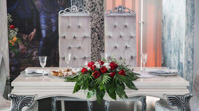 Романтический букет из красных роз на белом столе молодожёнов