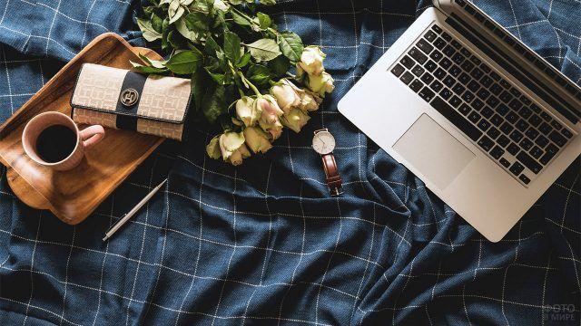 Розы на покрывале среди деловых предметов