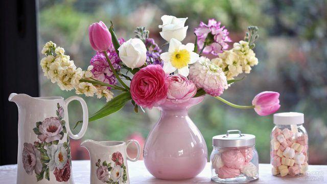 Садовые цветы в розовой вазе среди чайного сервиза и зефирок