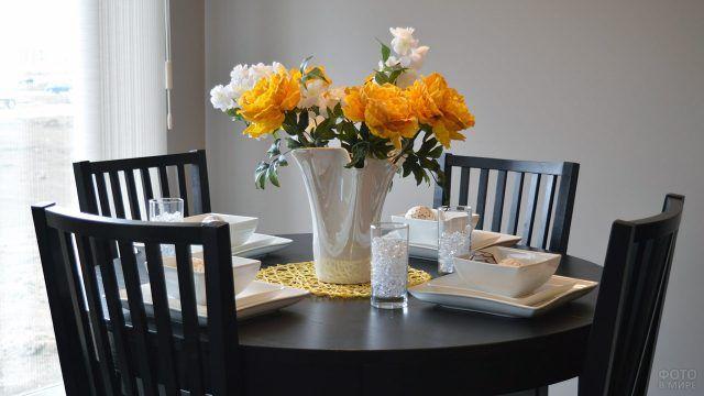Жёлтые цветы в белой вазе на столе цвета венге