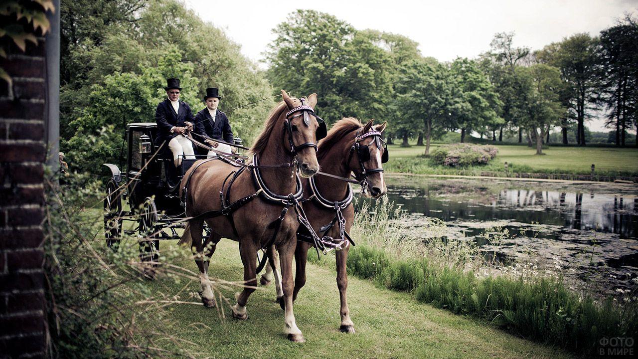 Мужчины в костюмах 18 века правят двойкой лошадей впряжённых в лаковое ландо