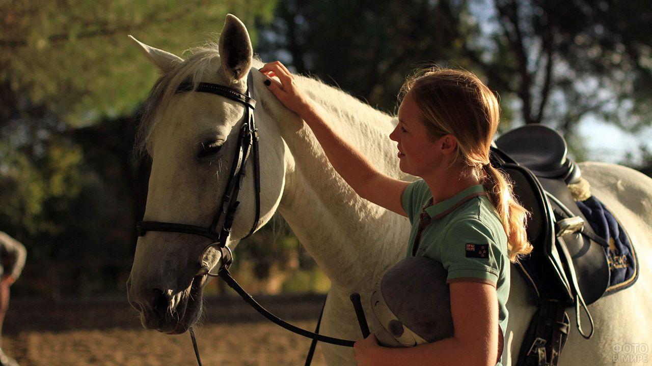 Светловолосая спортсменка гладит по холке белую лошадь