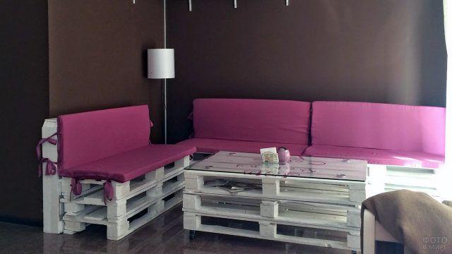 Белый паллетный диван с розовыми подушками