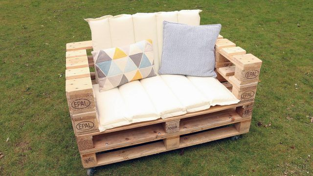 Декор паллетного дивана мягкими светлыми подушками