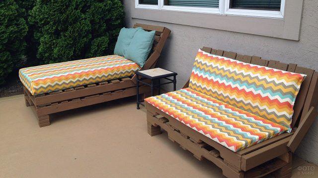 Мебель для патио из паллет с пёстрыми подушками