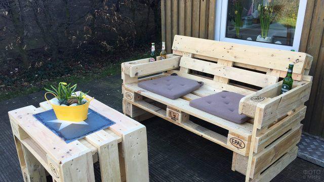 Садовая скамейка из паллетов с подставками в подлокотниках