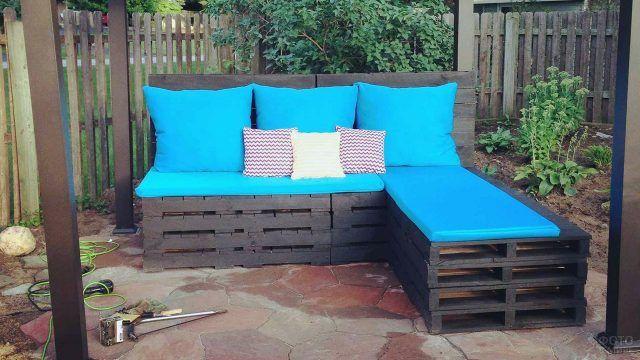Угловой диван цвета венге из поддонов с бирюзовыми подушками