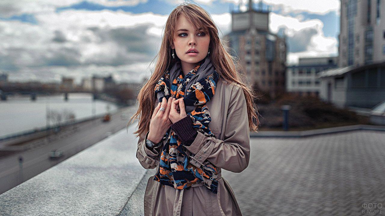 Девушка-модель в лёгком плаще с пёстрым шарфом на весенней улице