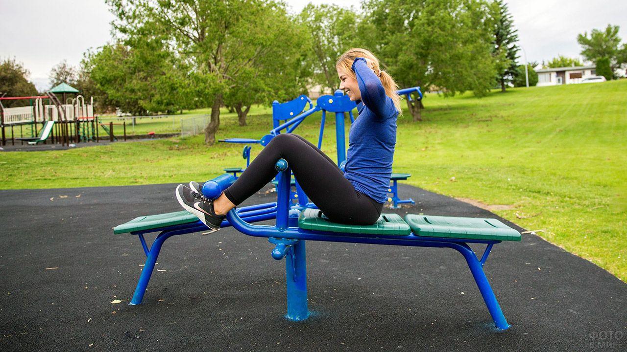 Девушка на фитнесс-скамейке в парке