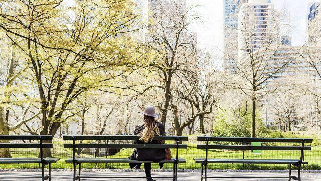 Девушка в шляпе на скамейке в городском парке